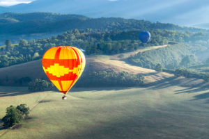Red and yellow hot air balloon floating through the Yarra Valley Global Ballooning Hot Air Ballooning Melbourne