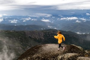 Girl in a yellow jacket jumping from rock to rock at Mount Buffalo